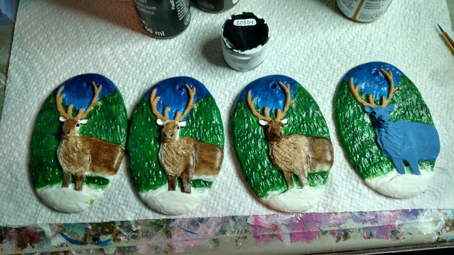 Four Resin Reindeer Ornaments being painted