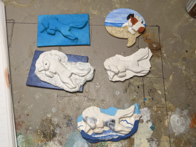 Work in progress photo of various plaster and wood Leaping Pony magnets.